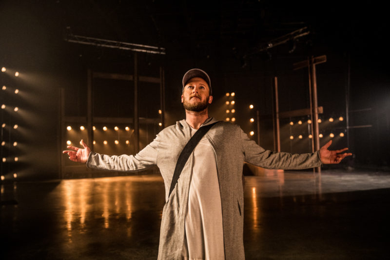 Jesus stands alone on stage wearing a baseball cap with his arms open wide